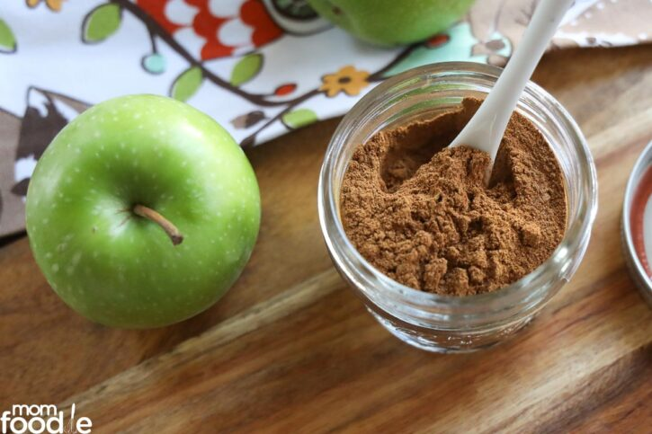 spices in jar with apple on side.