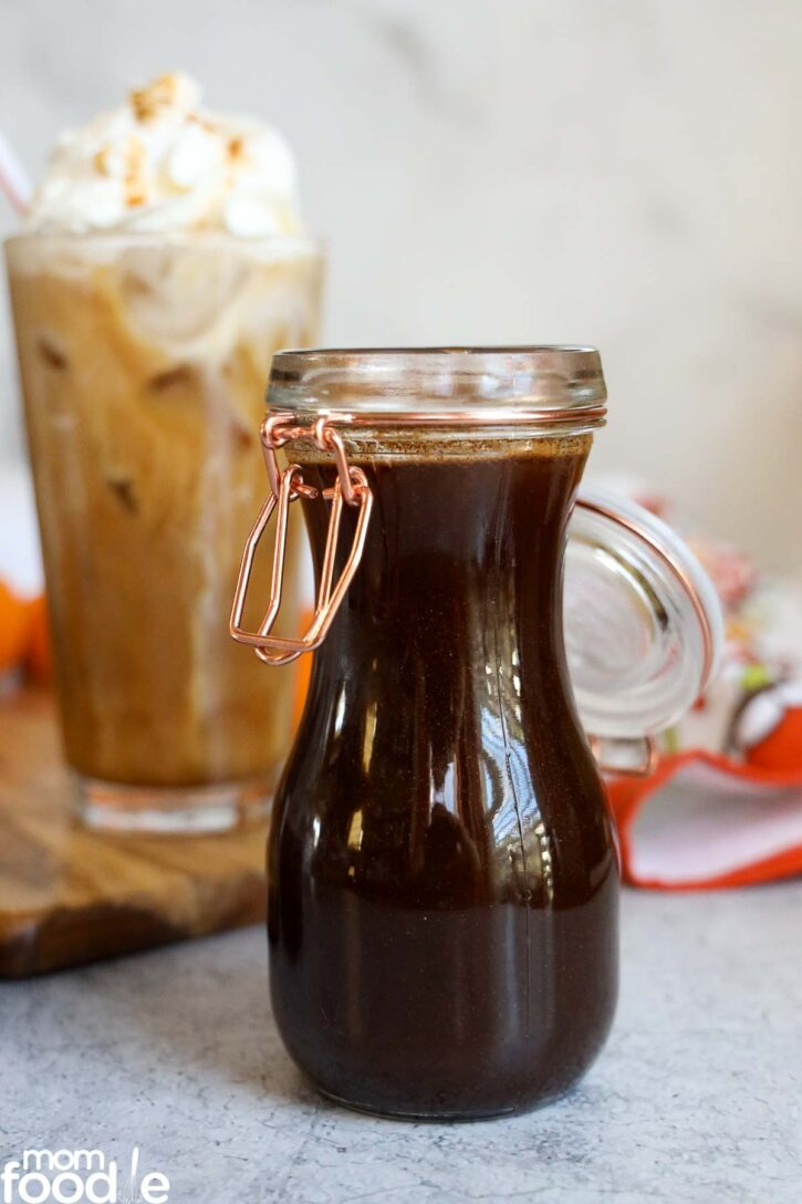 Pumpkin Spice Syrup in glass bottle with iced starbucks pumpkin spice latte coffee copycat in background.
