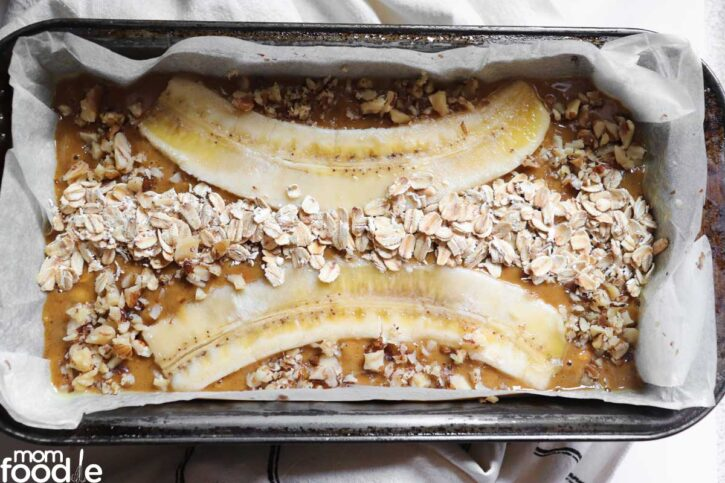 banana slices and oats on top of the banana date bread.