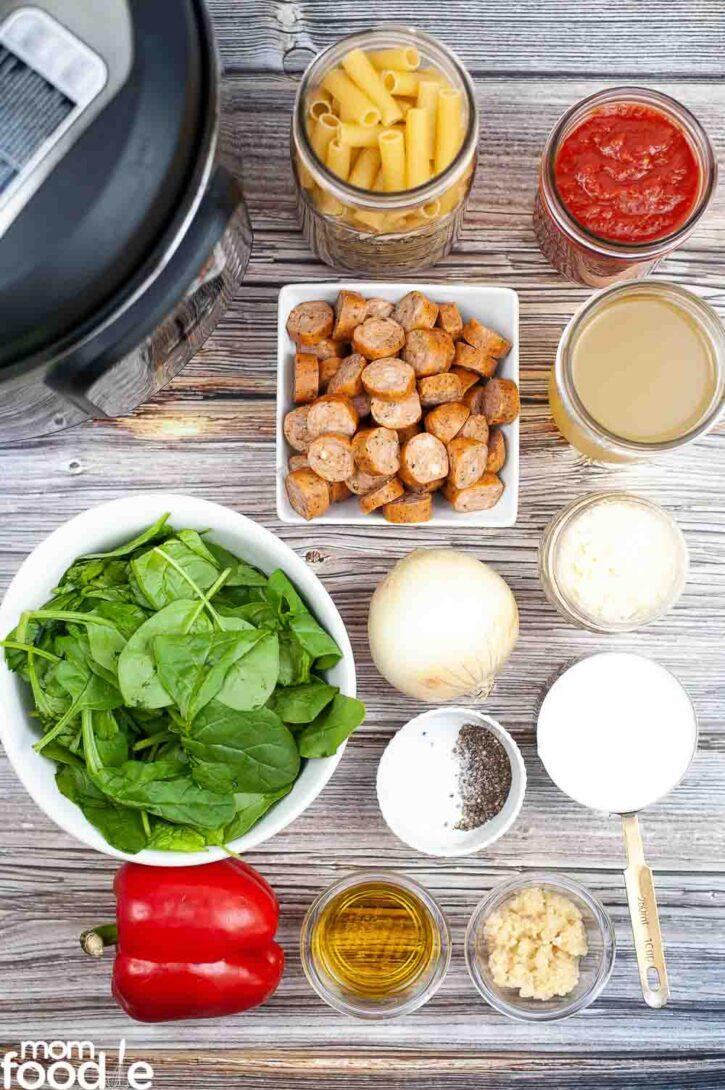 Ingredients for cheesy kielbasa Pasta on wood surface.