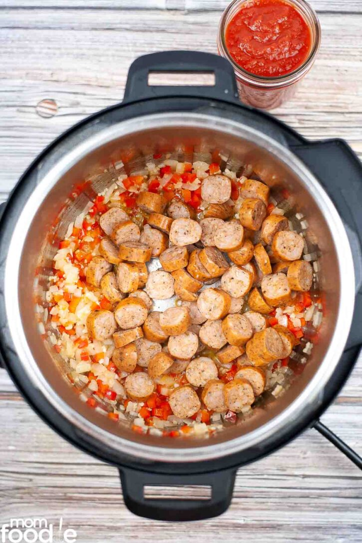 Kielbasa with peppers and onions being sauteed in the pressure cooker.