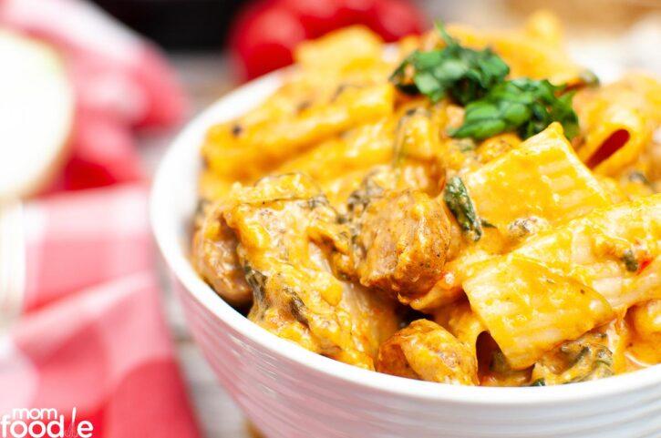 Creamy pasta with kielbasa sausage in bowl.