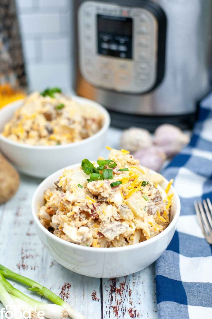 Instant Pot Potato salad loaded with bacon and cheese in bowls in front of Instant Pot.