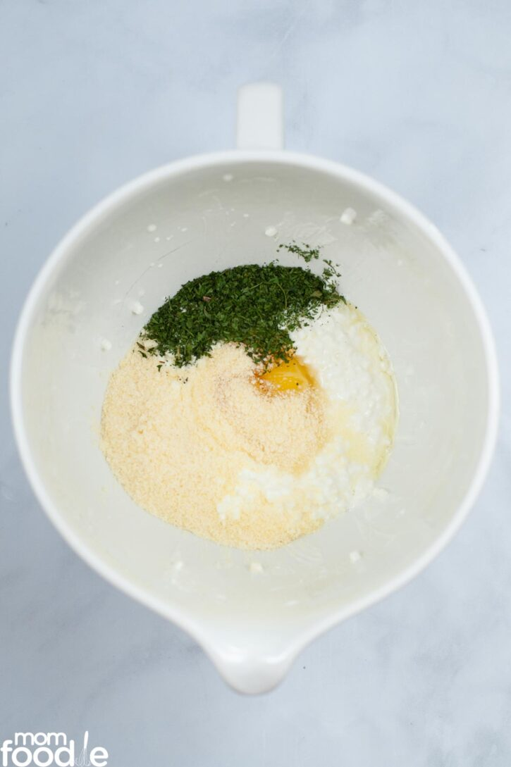 Ricotta cheese, Parmesan, eggs and 1 tablespoon of the parsley in medium bowl before mixing.