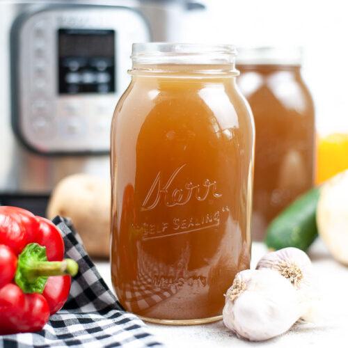 Vegetarian broth in mason jars in front of Instant Pot pressure cooker.