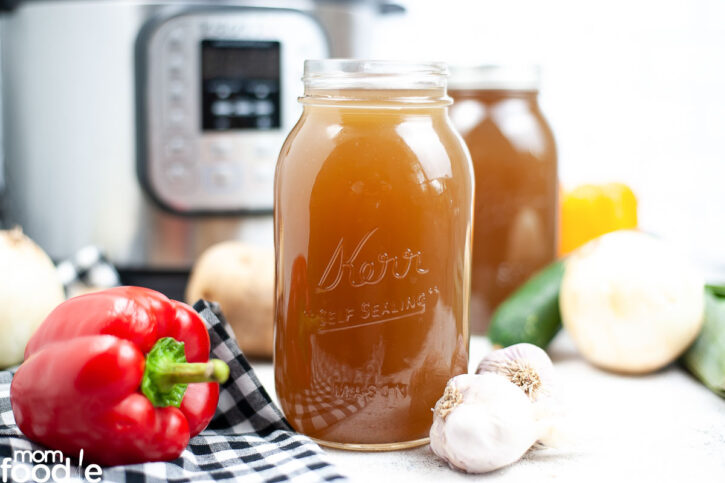 instant pot vegetable stock in glass jars for storage.