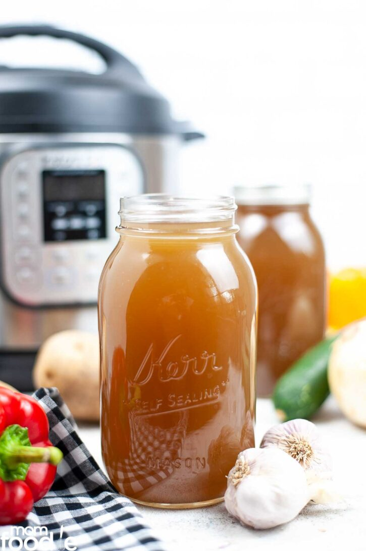 vegetable broth instant pot recipe in jars in front of pressure cooker.