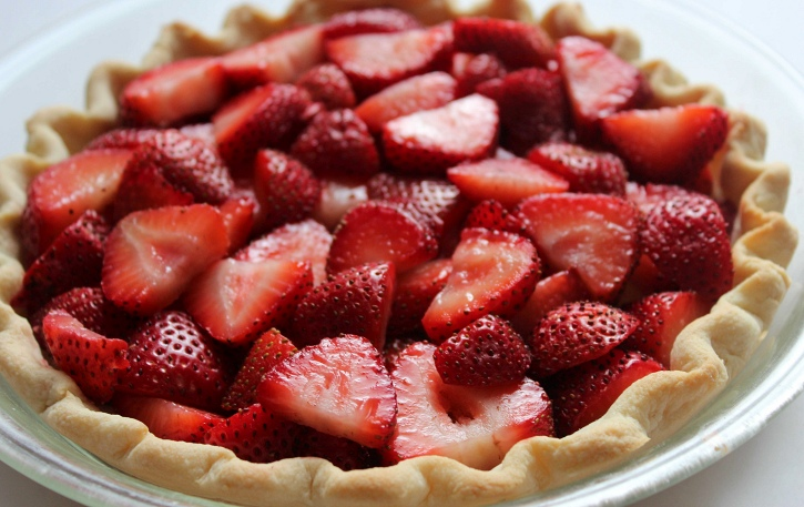 layering sliced strawberries in crust