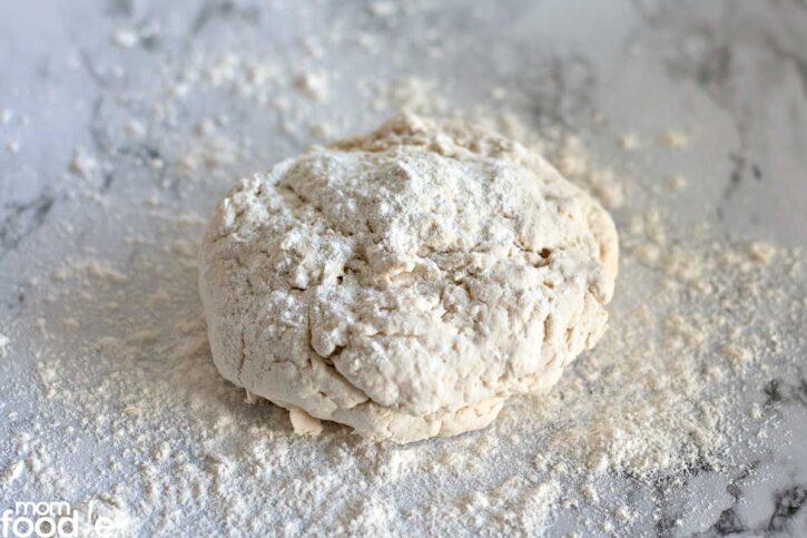 Kneading the pizza dough ball on a lightly floured surface.