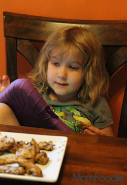 child eating grilled chicken