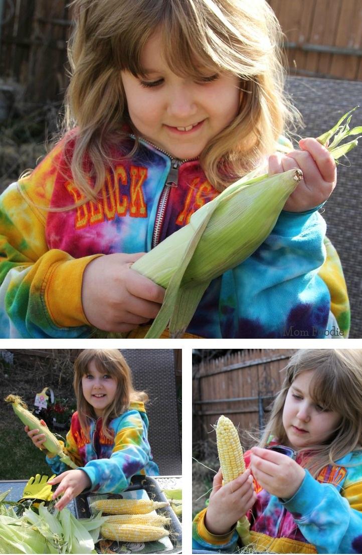 child husking sweet corn