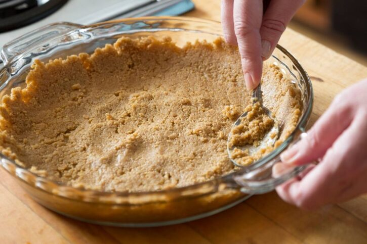 graham crust being spread out with spoon in glass pie dish